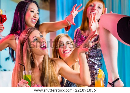 Drunk girls with fancy cocktails in strip club - stock photo