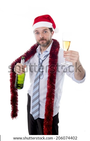 drunk happy attractive business man wearing santa hat with tinsel around neck in blue shirt and tie holding bottle and glass of champagne drinking at christmas party isolated on white background - stock photo