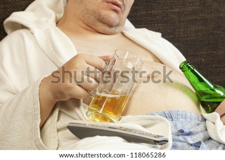Drunk man asleep with a beer in the hands of - stock photo