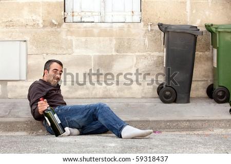 drunk man lying on city street near trashcan - stock photo