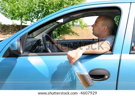 Drunk man sitting in drivers and holding a bottle alcohol