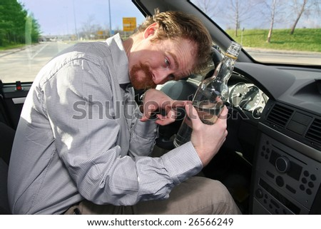 Drunk man sitting in drivers with a bottle alcohol - stock photo