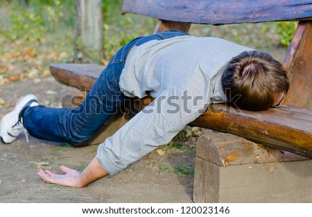 Drunk man sleeping in park on wooden bench - stock photo