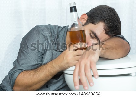 Drunk man sleeping on the toilet and holding a liquor bottle - stock photo