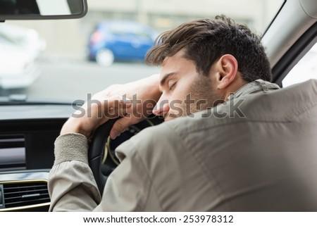Drunk man slumped on steering wheel in his car - stock photo