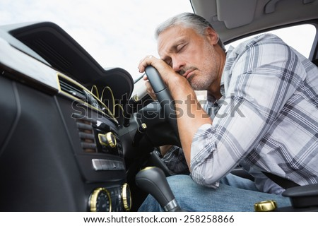 Drunk man slumped on steering wheel in his car - stock photo