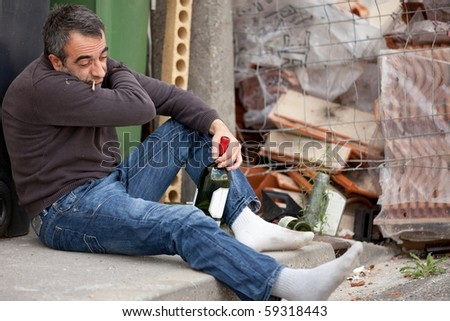 drunk tramp man sitting near trashcan holding bottle of wine - stock photo