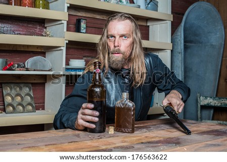 Drunk Western Man Looks Towards You as he Sits at Table - stock photo