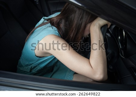 Drunk woman asleep at the wheel - stock photo