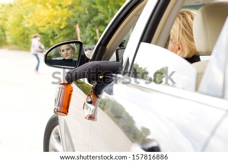 Drunk woman driver about to hit a pedestrian leaning to look out of the side window as she dangles her bottle of alcohol outdoors and taking her eyes off the road and the children playing up ahead - stock photo