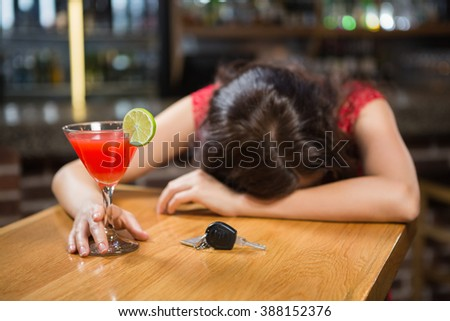 Drunk woman driver leaning on counter with her cocktail in a pub - stock photo