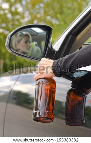 Drunk woman driver reflected in the side view mirror of the car dangling her arm through the open window clutching her bottle of booze - stock photo