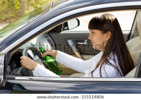 Drunk woman driver smiling as she drives with a bottle of alcohol clutched tightly in one hand, view through the side window - stock photo