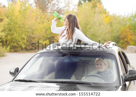 Drunk woman passenger in a car standing up through a sunroof drinking alcohol directly from a bottle as she continues her partying on the way home - stock photo