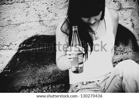 Drunk young girl with a bottle of beer in hand is sitting at the wall. Demonstration of youth social problems - stock photo