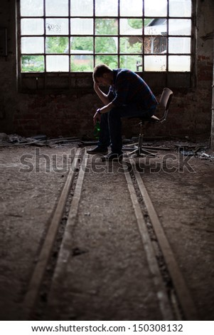 Drunk young man self-reflecting on his life in a dark abandoned industrial building - stock photo