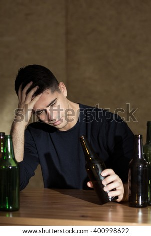Drunk, young man sitting beside bar table, holding bottle, empty bottles next to him - stock photo