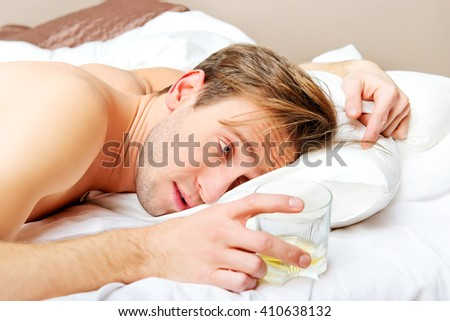 Drunken man lying on bed with glass of whisky
