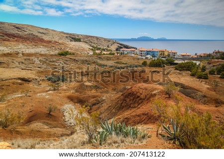 Dry and hot desert landscape near the ocean at Canical, Maderia. In the background the island Deserta Grande can be seen on the horizon - stock photo