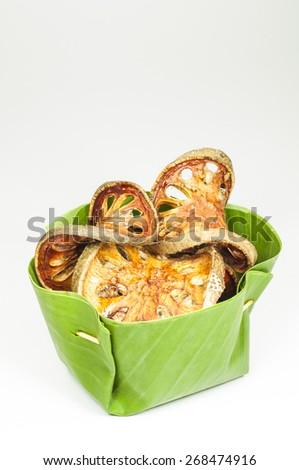 Dry Bael Fruit tea (Aegle marmelos) banana leaf cup. on white background. - stock photo