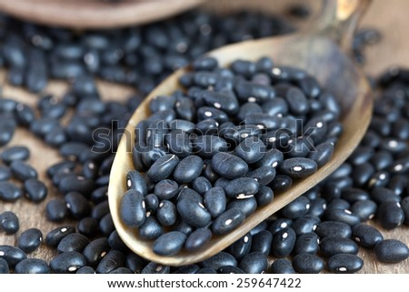 Dry black small beans in a clay bowl and in a scoop on wooden table, selective focus - some beans in focus, some are not. Macro - stock photo
