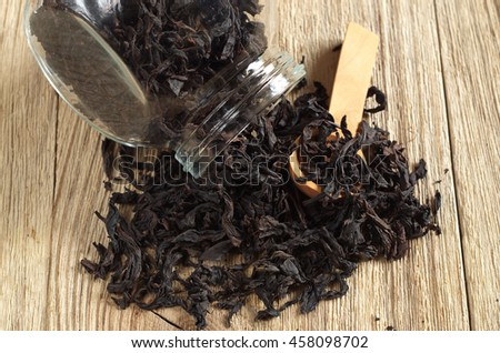 Dry black tea in glass jar and scattered on the wooden table