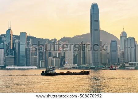 Dry cargo vessel at Victoria Harbor of Hong Kong at sunset. View from Kowloon on HK Island.