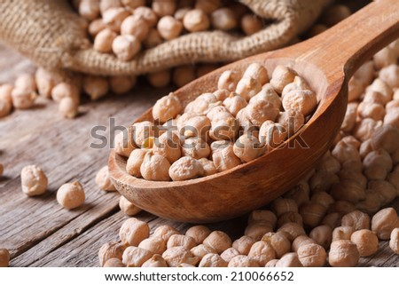 Dry chickpeas close up in a wooden spoon on a background of peas in a bag. horizontal - stock photo