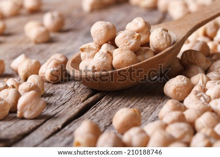 dry chickpeas in a wooden spoon close-up and scattered on the old table horizontal   - stock photo