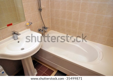 Dry, clean bathtub and wash basin in a luxurious hotel room - stock photo
