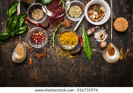 Dry colorful  spices in spoons and bowls with fresh seasoning on dark rustic wooden background, top view, border - stock photo