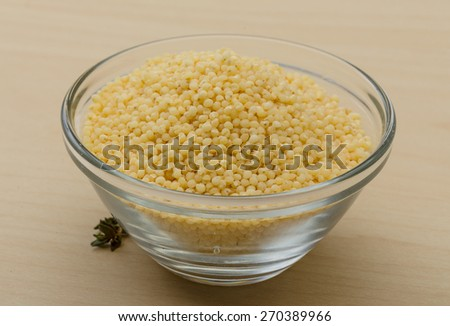 Dry couscous pile on the glass bowl - stock photo