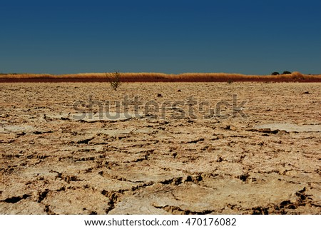 Dry cracked desert landscape with blue sky