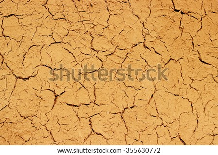 Dry cracked mud wall background texture pattern. Background texture pattern of dried , cracked dirt/ soil in rural nature. - stock photo