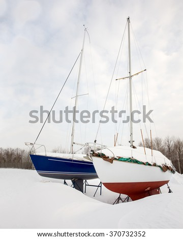 Dry Docked Sailboats - Two sailboats side by side in the snow.  Stored on land for winter.  Waiting for Spring. - stock photo