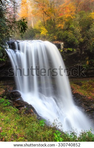 Dry Falls, also known as Upper Cullasaja Falls, is a 65 foot waterfall in the Nantahala National Forest, northwest of Highlands, North Carolina in autumn. - stock photo