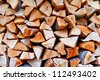 Dry firewood stacked in a row, one above the other. - stock photo