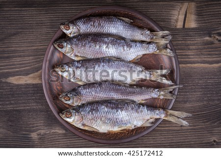 Dry fish on a wooden background, close up