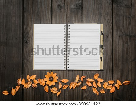 Dry flowers and white blank page sketch book on wood table - stock photo