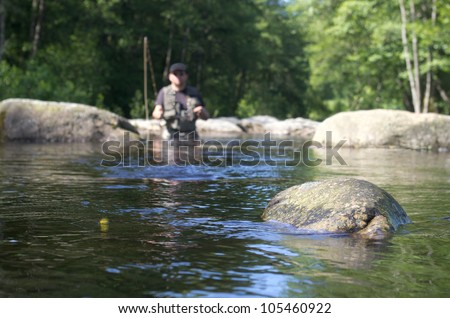 Dry fly fishing. Fly fishermen in a French trout river. Fishing scene focused on fly fishing lure - stock photo