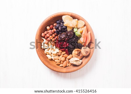 Dry fruits and nuts in bowl on wooden table. Copy space background - close up healthy sweets - stock photo