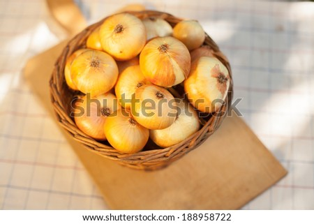 Dry golden onions ina brown basket and cutting wood - stock photo
