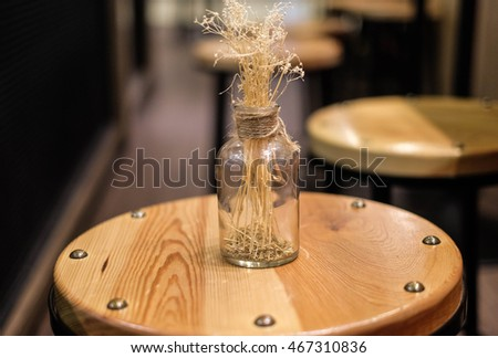 Dry grass brown color in the glass bottle set on the wood chair, interior design in coffee cafe, straw