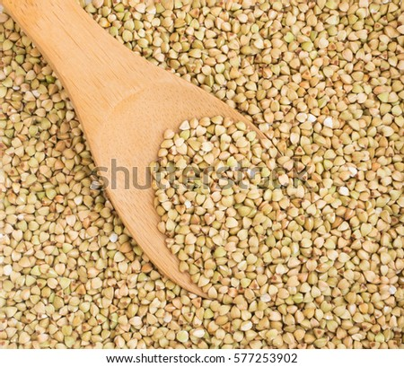 Dry Green Buckwheat Grain in Wooden Spoon. Healthy Cereal Vegetarian or Vegan Food