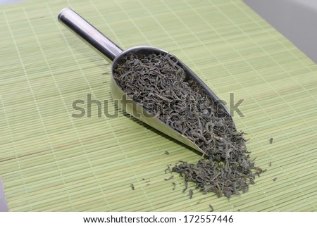 Dry green tea in the wooden spoon - stock photo