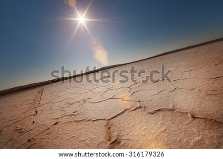 Dry lake under a blue sky and a bright sun