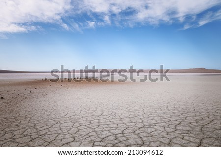 Dry lake under blue sky with clouds - stock photo