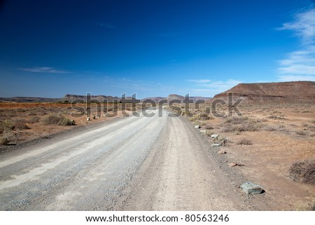 Dry landscape in South Africa with a lonely road or highway with a vision and a clear blue sky - horizontal - stock photo