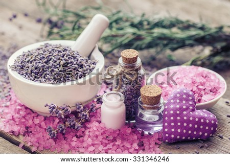 Dry lavender flowers in mortar, sea salt, cream, essential oil and decorative heart. Selective focus.  - stock photo