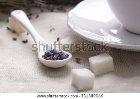 Dry lavender flowers. Lavender tea in white ceramic spoon with pieces of sugar, textile background. ?up of herbal tea with a lavender bouquet on linen fabric.  - stock photo